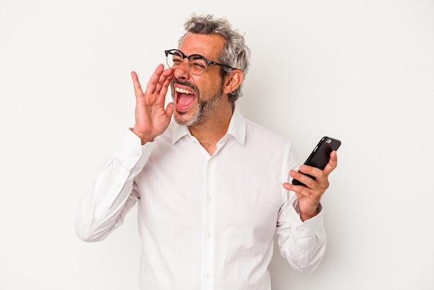 Homem de negócios caucasiano de meia-idade, segurando um telefone móvel isolado no fundo branco, gritando e segurando a palma da mão perto da boca aberta.