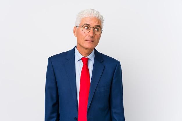 Homem de negócios caucasiano envelhecido médio isolado confuso, sente-se duvidoso e inseguro.