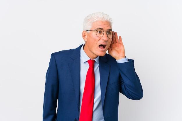 Homem de negócios caucasiano envelhecido médio isolado tentando ouvir uma fofoca.