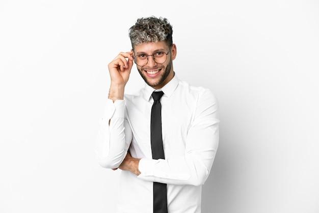 Homem de negócios caucasiano isolado no fundo branco com óculos e feliz