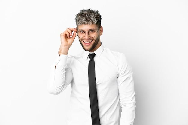 Homem de negócios caucasiano isolado no fundo branco com óculos e surpreso