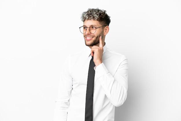 Homem de negócios, caucasiano, isolado no fundo branco, pensando em uma ideia enquanto olha para cima