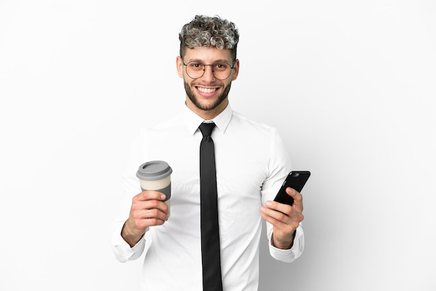 Homem de negócios, caucasiano, isolado no fundo branco, segurando um café para levar e um celular