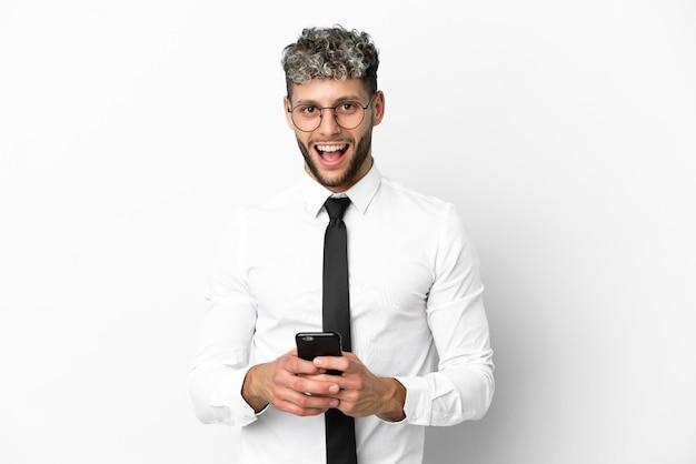 Homem de negócios caucasiano isolado no fundo branco surpreso e enviando uma mensagem