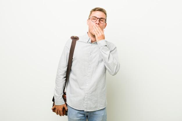 Homem de negócios caucasiano jovem bocejando mostrando um gesto cansado, cobrindo a boca com a mão.