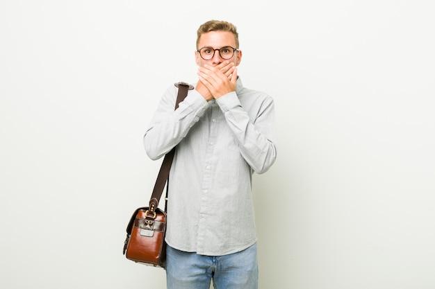Homem de negócios caucasiano jovem chocado cobrindo a boca com as mãos.
