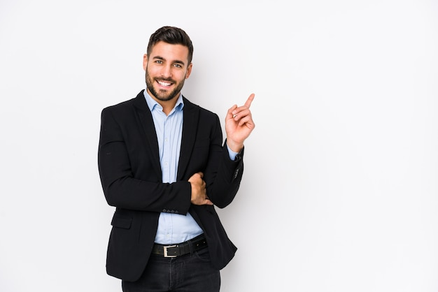 Homem de negócios caucasiano jovem contra uma parede branca, sorrindo alegremente apontando com o dedo indicador fora.