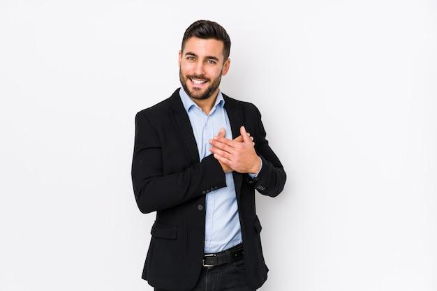 Homem de negócios caucasiano jovem contra uma parede branca tem expressão amigável, pressionando a palma da mão no peito.