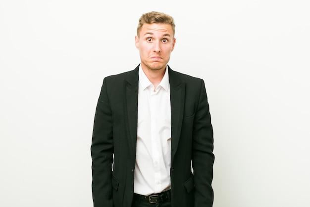Homem de negócios caucasiano jovem encolhe os ombros e abre os olhos confusos.