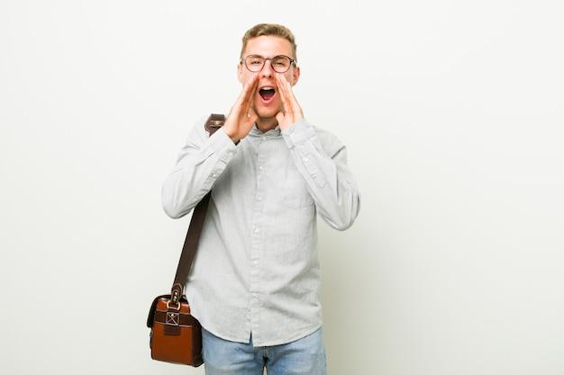Homem de negócios caucasiano jovem gritando animado para a frente.