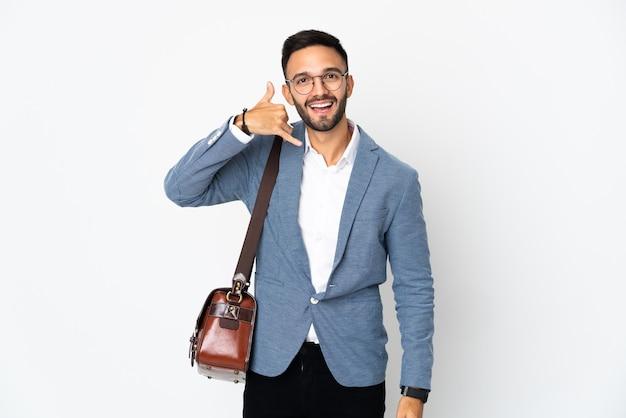 Homem de negócios caucasiano jovem isolado na parede branca, fazendo gesto de telefone. ligue-me de volta sinal