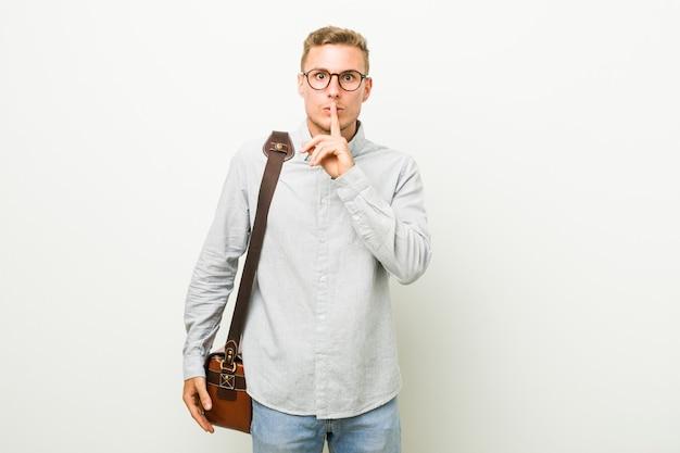 Homem de negócios caucasiano jovem mantendo um segredo ou pedindo silêncio.