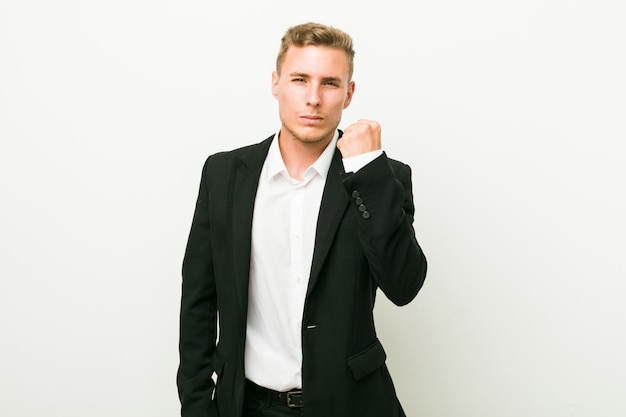 Homem de negócios caucasiano jovem mostrando o punho, expressão facial agressiva.