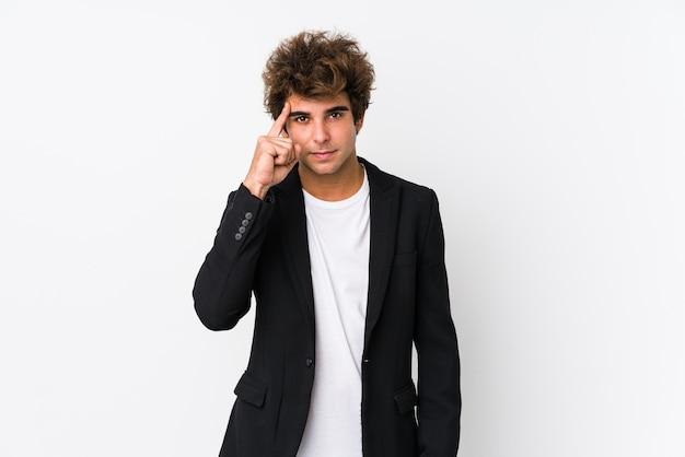 Homem de negócios caucasiano jovem no templo apontando isolado branco com o dedo, pensando, focado na tarefa.