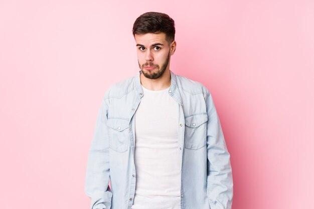 Homem de negócios caucasiano jovem posando em um branco isolado encolhe os ombros e abre os olhos confusos.