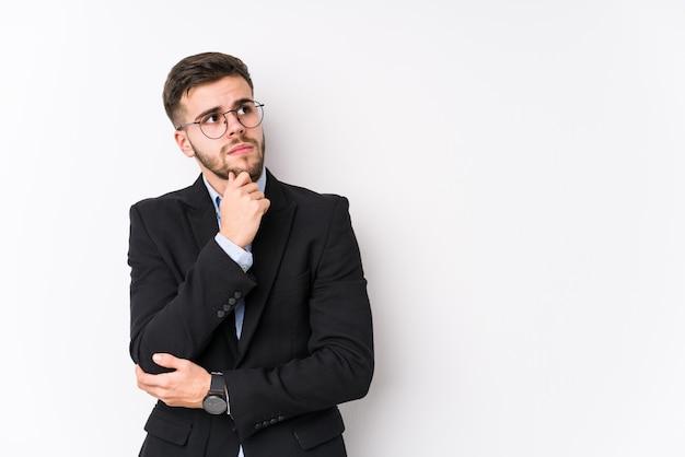 Homem de negócios caucasiano jovem posando em uma parede branca isolada homem de negócios caucasiano jovem olhando de soslaio com expressão duvidosa e cética.