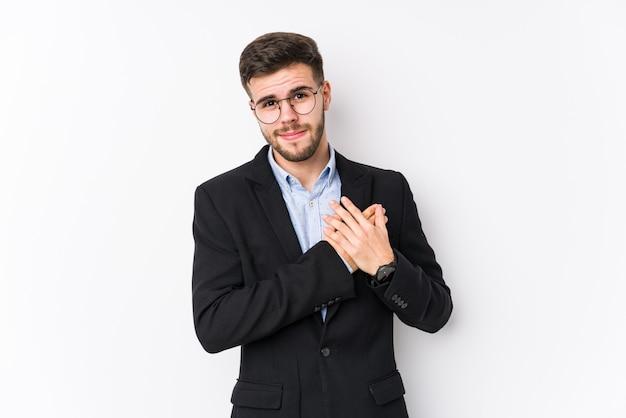 Homem de negócios caucasiano jovem posando em uma parede branca isolada homem de negócios caucasiano jovem tem expressão amigável, pressionando a palma da mão no peito. conceito de amor