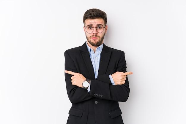 Homem de negócios caucasiano jovem posando em uma parede branca isolada o homem de negócios caucasiano jovem aponta lateralmente, está tentando escolher entre duas opções.