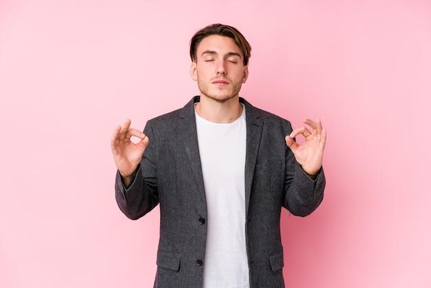 Homem de negócios caucasiano jovem posando isolado relaxa após um árduo dia de trabalho, ela está realizando ioga.