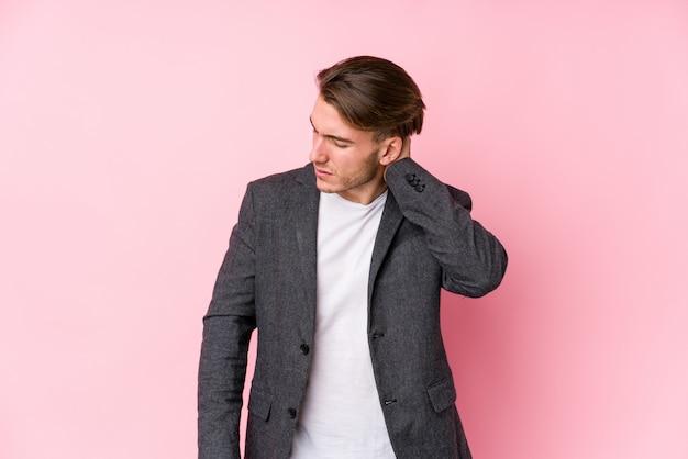 Homem de negócios caucasiano jovem posando isolado sofrendo dor no pescoço devido ao estilo de vida sedentário.
