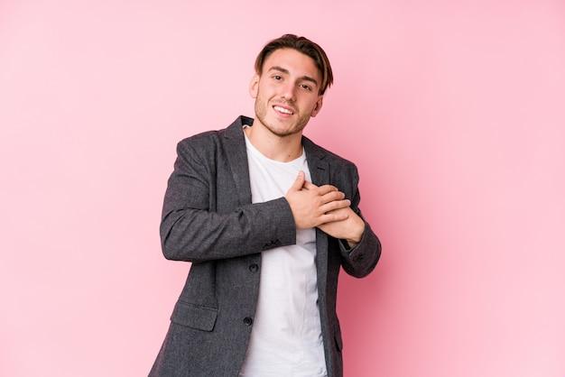 Homem de negócios caucasiano jovem posando isolado tem expressão amigável, pressionando a palma da mão no peito. conceito de amor