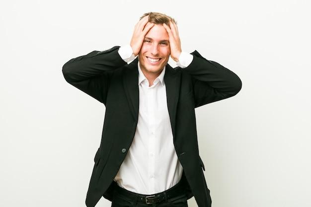 Homem de negócios caucasiano jovem ri alegremente, mantendo as mãos na cabeça. conceito de felicidade.