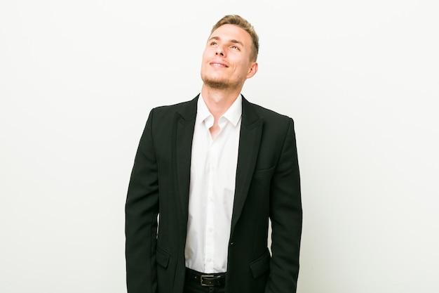 Homem de negócios caucasiano jovem sonhando em alcançar metas e propósitos