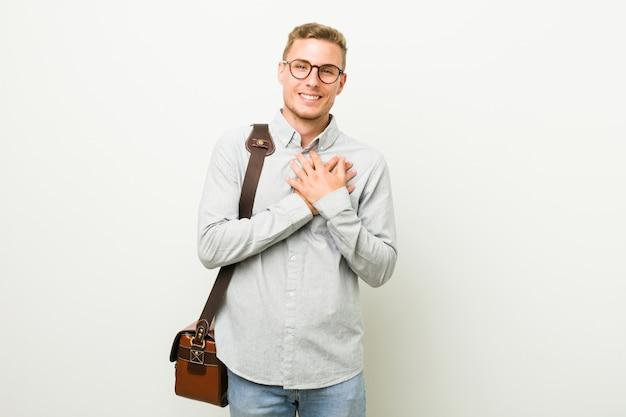 Homem de negócios caucasiano jovem tem expressão amigável, pressionando a palma da mão no peito. conceito de amor