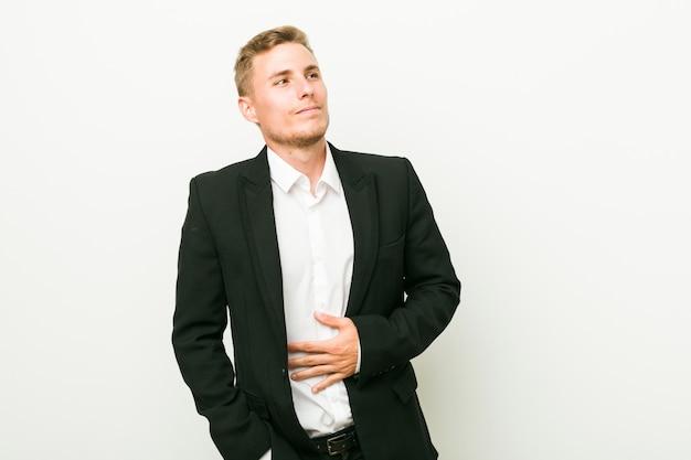 Homem de negócios caucasiano jovem toca barriga, sorri suavemente, comer e conceito de satisfação.