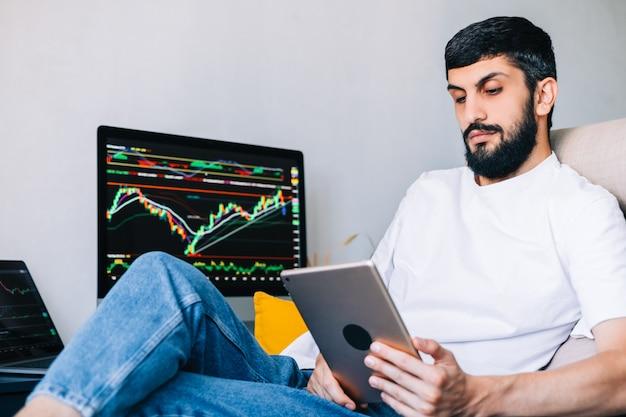 Homem de negócios caucasiano negociando online, usando tecnologia de computador, olhando para o comércio da bolsa de valores e analisando