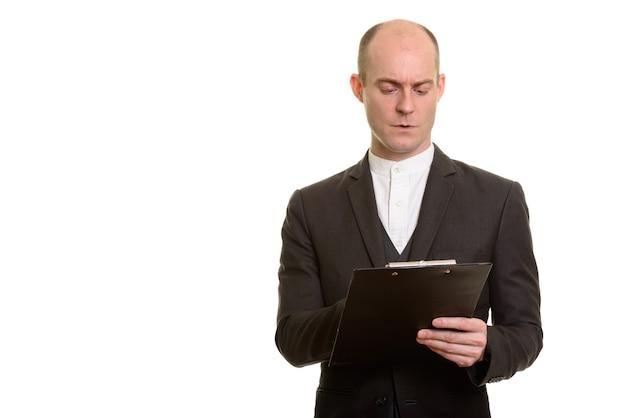 Homem de negócios caucasiano sério e careca lendo na prancheta