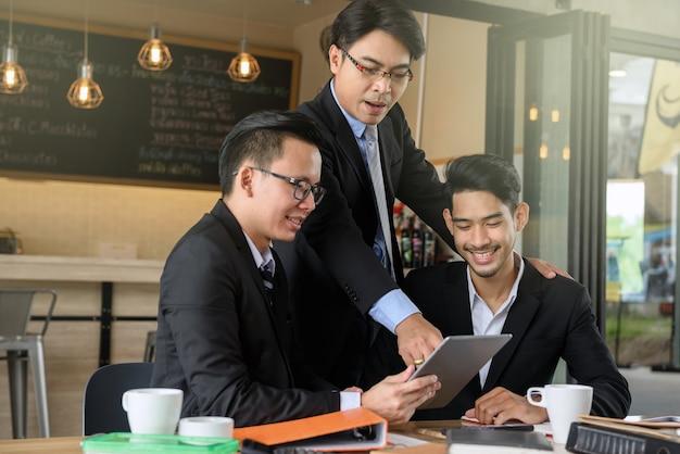 Homem de negócios chefe treinando dois jovem empresário feliz por tablet digital