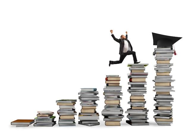 Homem de negócios chega ao chapéu de formatura pulando em pilhas de livros