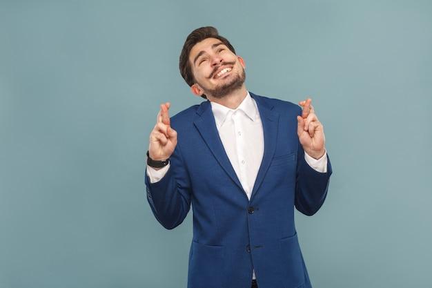 Homem de negócios cheio de dentes sorrindo com os dedos cruzados, desejo orar e ter esperança