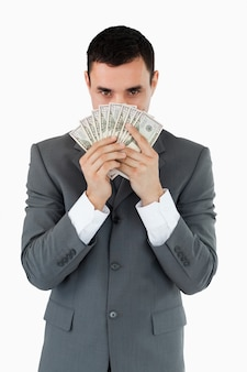 Homem de negócios cheirando notas bancárias