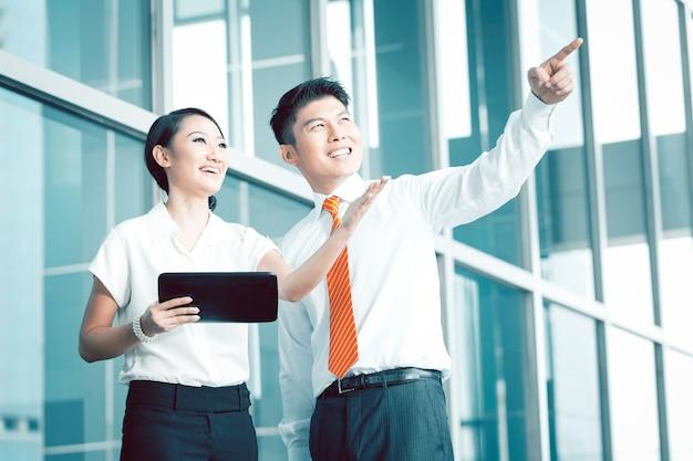 Homem de negócios chinês explicando sua visão ou idéia para colega