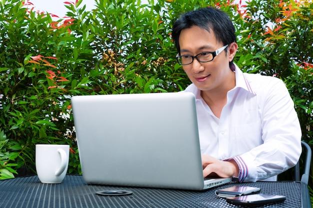 Homem de negócios chinês trabalhando ao ar livre