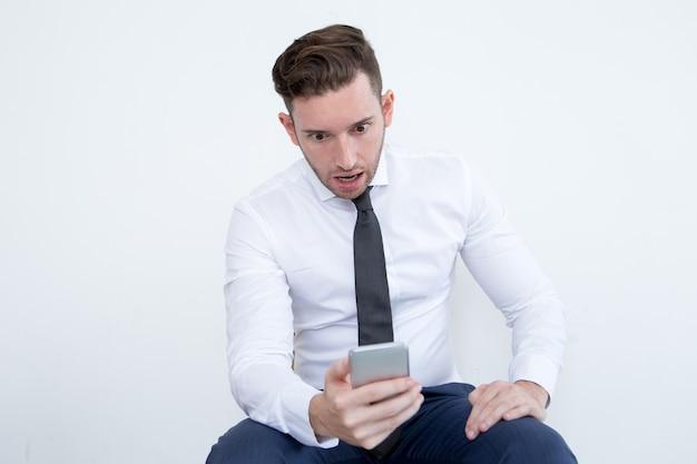 Homem de negócios chocado lendo notícias no telefone