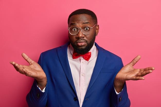 Homem de negócios chocado sem noção tem hesitação, expressa incerteza, intrigado com o que fazer melhor, usa óculos ópticos, terno formal, gravata borboleta vermelha