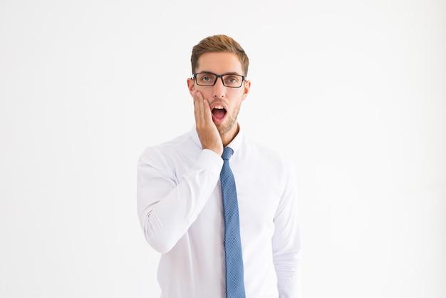 Homem de negócios chocado tocando a bochecha com a boca aberta