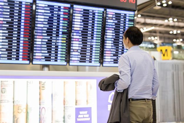 Homem de negócios com a mochila no aeroporto perto de voo