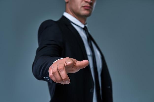 Homem de negócios com apontar para algo ou tocar em uma tela de toque em fundo cinza.