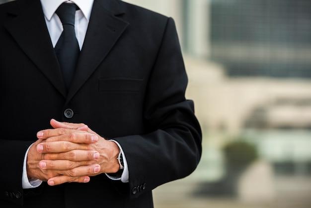 Homem de negócios com as mãos entrelaçadas