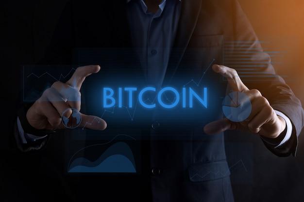 Homem de negócios com as mãos segurando a inscrição bitcoin com gráficos diferentes
