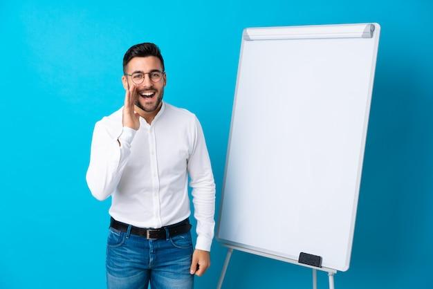 Homem de negócios com barba com quadro branco sobre parede isolada