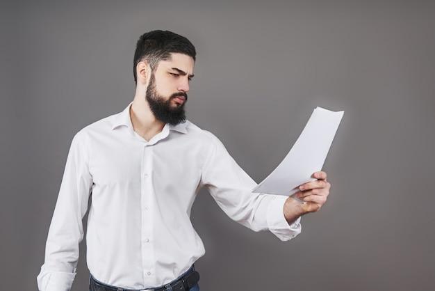 Homem de negócios com barba na camisa branca segurando documentos em cinza