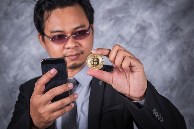 Homem de negócios com bitcoin e usando telefone celular