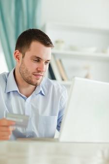 Homem de negócios com cartão de crédito e laptop em sua casa