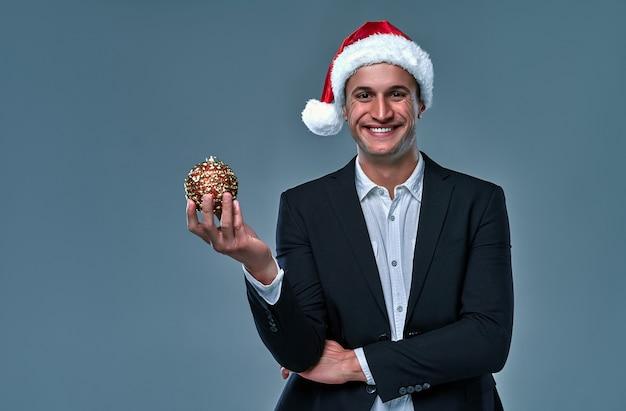 Homem de negócios com chapéu de natal detém bola decorativa de natal ou natal isolada em um fundo cinza.