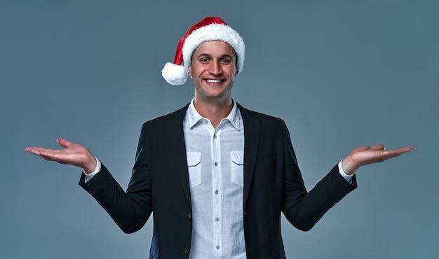 Homem de negócios com chapéu de natal segurando cópia espaço em branco vazio no desconto de venda de anúncio de duas palmas isolado sobre um fundo cinza e sorrindo.